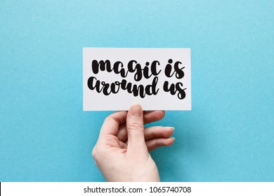 Minimal composition on a blue pastel background with girl's hand holding card with quote - Magic is around us