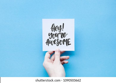Minimal composition on a blue pastel background with girl's hand hold card with quote - Hey! You're awesome