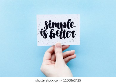 Minimal composition on a blue pastel background with girl's hand hold card with quote - Simple is better