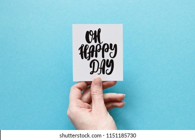 Minimal composition on a blue pastel background with girl's hand holding card with quote - Oh happy day