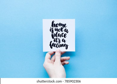 "Minimal composition on a blue pastel background with girl's hand holding card with quote ""home is not a place it's a feeling"" written in calligraphy style"