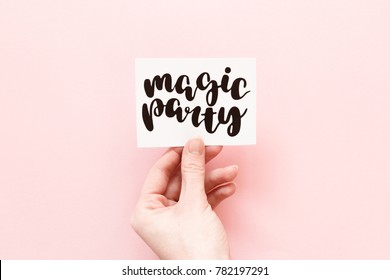 "Minimal composition on a pale pink pastel background with girl's hand holding card with handwritten quote ""magic party"""