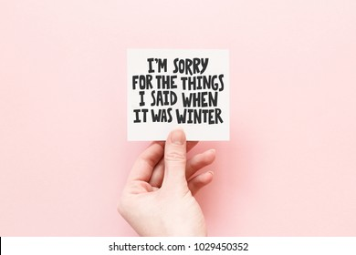 Minimal composition on a pink pastel background with girl's hand holding card with quote - I'm sorry for the things I said when it was winter
