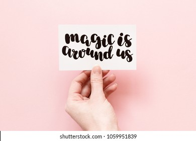 Minimal composition on a pink pastel background with girl's hand holding card with quote - Magis is around us