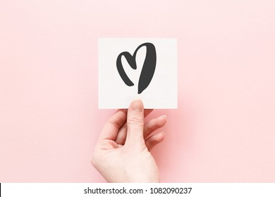 Minimal composition on a pink pastel background with girl's hand holding card with hand drawn heart