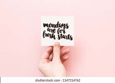Minimal composition on a pink pastel background with girl's hand holding card with quote - Mondays are for fresh starts