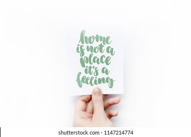 Minimal composition on a white background with girl's hand holding card with quote -  Home is not a place it's a feeling