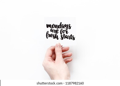 Minimal composition on a white background with girl's hand hold card with quote - Mondays are for fresh starts