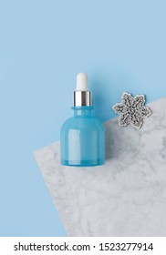 Minimal composition with serum or oil in blue glass bottle with dropper on creative background. Winter skin treatment concept