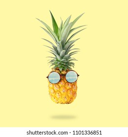 minimal concept. Cute and funny pineapple with sunglasses over pastel yellow background
