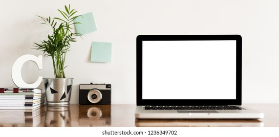 Minimal desk with laptop white screen, stationery, books and houseplant. Home ofice workspace.