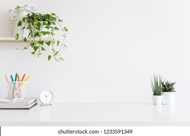 Minimal desk, office supplies and plants on white wall. Copy space for product display montage.