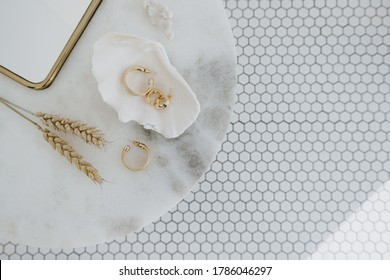 Minimal fashion composition with golden earrings in seashell on marble table with mirror and wheat stalks. Flat lay, top view bijouterie / jewelry concept on mosaic tile background.
