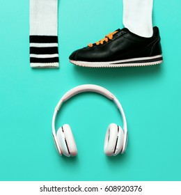 Minimal fashion creative art. Urban street vibrations. Music and sports. Sneakers and headphones.