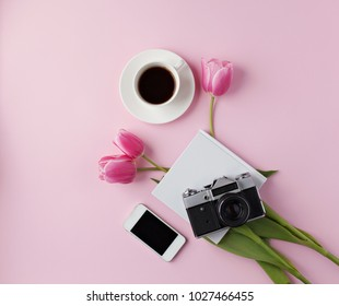 Minimal feminine home desktop with coffee mug, mobile phone and old camera on pink background. Flat lay, top view.
