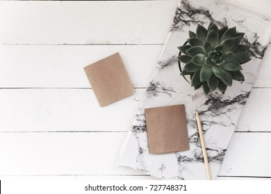 Minimal flat table,cactus,notebook,marble plaque on pastel background for copy space. top view