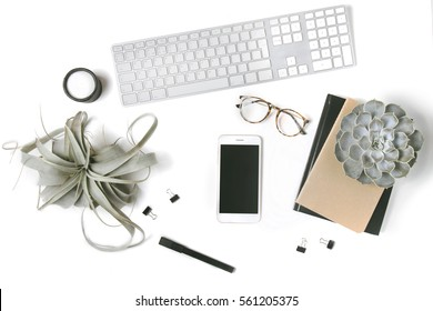 Minimal flatlay with smartphone, candle, eyeglasses, notebooks, keyboard, paper clips, pen and succulent plants isolated on white background. Feminine workspace desktop top view. Mock up