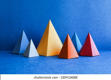 Minimal geometric still life background. Platonic solid geometric figures. Three-dimensional pyramid rectangular triangle objects on blue background.