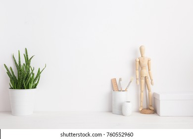 Minimal home decor mock up. Creative desk with wooden manequin, desk objects, office supplies, box and plant on a white background.