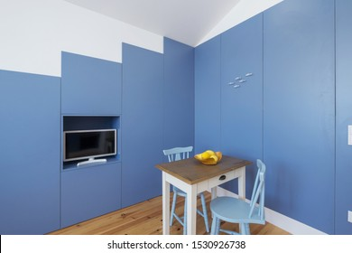 Minimal interior design kitchen in small apartment. Blue walls, yellow lemons on little table