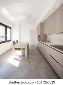 Minimal kitchen in a modern apartment with chairs and table. Nobody iniside