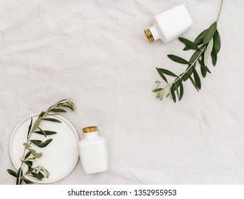 Minimal lifestyle background. Flat lay composition with ceramic bottles and olive branches on linen