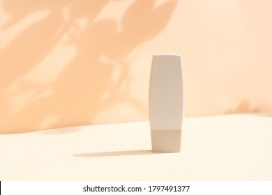 Minimal modern cosmetic product display on textured beige background with shadow overlay