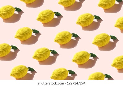 Minimal nature pattern with artisan crochet lemons and pastel pink background. Flat lay summer concept.