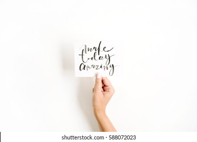 Minimal pale composition with girl's hand holding card with quote Make Today Amazing written in calligraphic style on paper on white background. Flat lay, top view