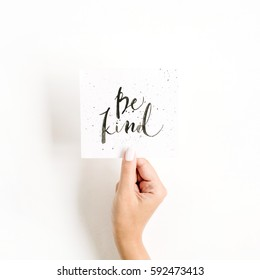 Minimal pale composition with girl's hand holding card with quote Be Kind written in calligraphic style on paper on white background. Flat lay, top view