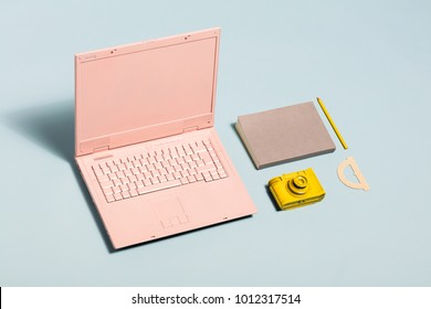 Minimal pastel workspace equipment. Pink laptop, yellow camera, notebook. Millennial lifestyle.