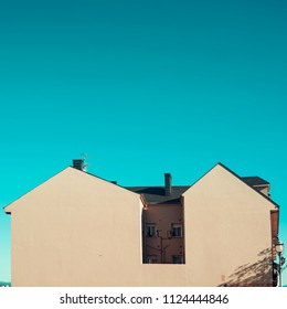 Minimal picture of a house with huge wall without any windows. The building is lighten by the daylight and under a blue intense sky.