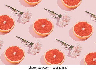 Minimal romatic pattern made with pink flowers and grapefruit on pastel background. Creative spring romance composition.