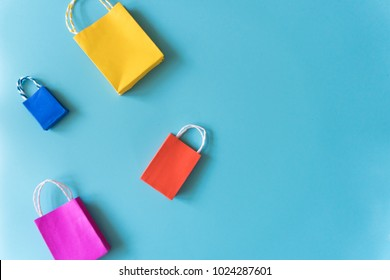 Minimal shopping online concept, Colorful paper shopping bag go down from floating blue background for copy space. Customer can buy everything form home and the messenger will deliver.