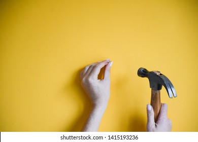 Minimal shot of woman's hands using a hammer to drive a nail into a yellow wall