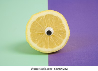 Minimal still life photography.An lemon cut in half and wearing doll's eyes like a cyclop. pop bi colored background : turquoise and purple