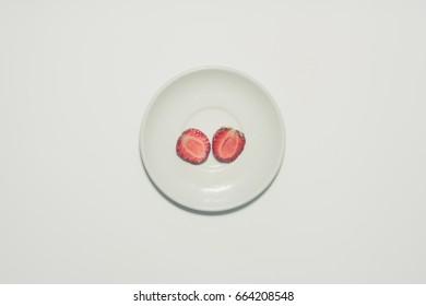 Minimal strawberry slice background. Fruit on white plate.