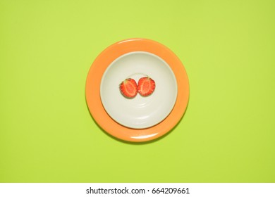 Minimal strawberry slice background. Fruit on white and orange colored plate with leaves around it.