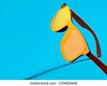 Minimal style closeup photography of  orange mirror sunglasses on blue background. Minimalist summer fashion or vacation concept. Eye protection.