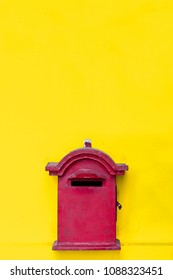 minimal style concept of red postal box on bright yellow grungy wall