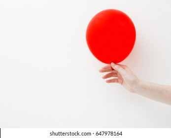 Minimal style. Minimalist photography. Hand holding a red balloon on a white wall background with shadow reflection