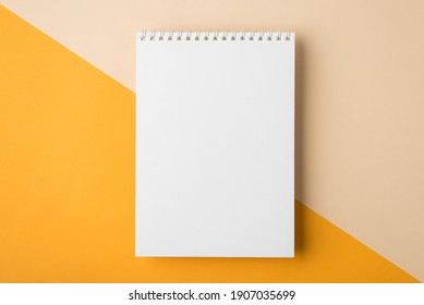 Minimal style note pad. Above overhead close up flat lay photo of clear spiral notepad with copy place for design isolated half yellow and beige backdrop desktop