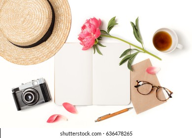 Minimal styled flat lay isolated on white background. Feminine desk top view summer accessories: hat, vintage photo camera, notebook mock up, glasses, envelope, coffee Creative diary. Travel concept