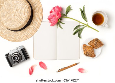 Minimal styled flat lay isolated on white background. Feminine desk top view with summer accessories: hat, vintage photo camera, notebook mock up, croissant, coffee Creative diary. Travel concept