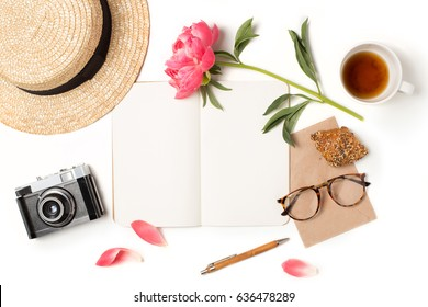 Minimal styled flat lay isolated on white background. Feminine desk top view summer accessories: hat, vintage photo camera, notebook mock up, glasses, croissant, coffee Creative diary. Travel concept