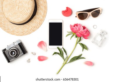 Minimal styled flat lay isolated on white background. Feminine desk top view with summer accessories: straw hat, sunglasses, vintage photo camera, perfume, smartphone mock up. Holiday app presentation