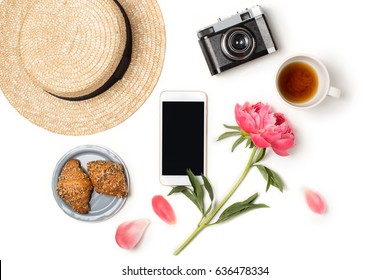 Minimal styled flat lay isolated on white background. Feminine desk top view with summer accessories: hat, vintage photo camera, smartphone mock up, croissant, coffee Summer holiday app presentation