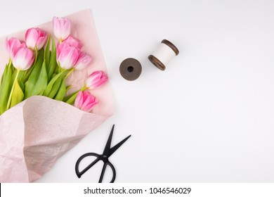 Minimal styled flat lay with pink tulips flowers with petals in pink paper wrapper, two thread spool and black scissors. Mock up top view isolated on white. Feminine flat lay.