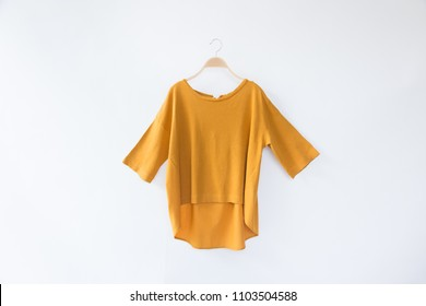 Minimal style.Yellow woman clothes is clothes hanger on white background.close up