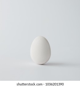 Minimal white Easter egg on bright background. Flat lay.